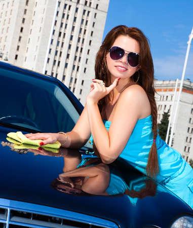 washing hair: Young woman washing car. Camera angle view.