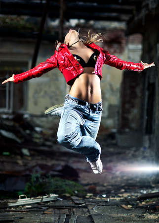 Young woman dancing on industrial background. photo