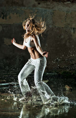 slum: Young woman dancing on street with water.