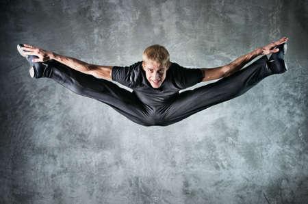 gimnasia: Joven bailar�n salto alto. En la fondo de pared.
