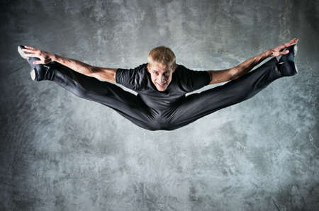 lithe: Young man dancer jumping up high. On wall background. Stock Photo