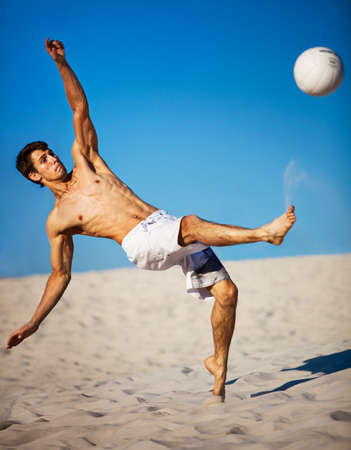 kicking ball: Young man playing soccer on beach. Focus on face.