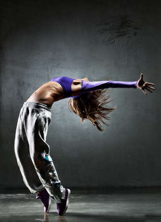 Young woman dancer. On wall background. photo