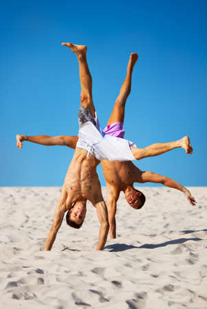 acrobatics: Two sportsmans on beach. On blue sky background.