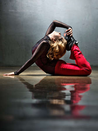 lithe: Young sports woman stretching on floor.
