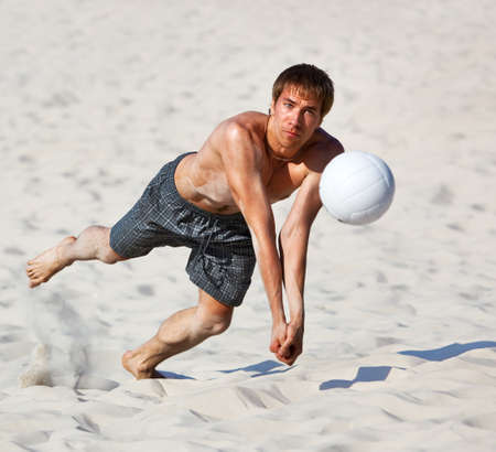 beach volleyball: Young man catching ball in volleyball game.