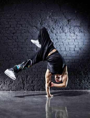Young strong man break dance. On dark wall background. photo