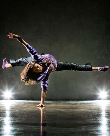 hip hop dancing: Young woman dancer. On wall background.