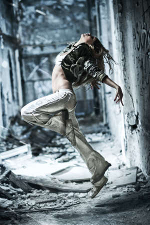 ruin: Young woman dancing on industrial background. Stock Photo