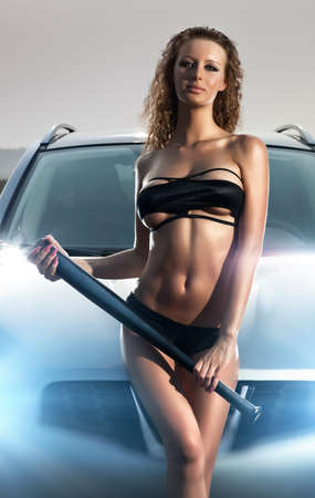 Young sexy woman with bat on car background. Stock Photo - 8016871