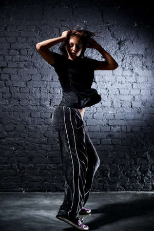 Young woman dancer. On wall background. Stock Photo - 8083696