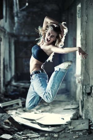 hiphop: Young woman jumping on industrial background. Stock Photo