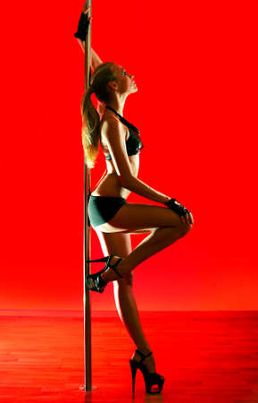 Young sexy pole dance woman. Vibrant red light. Stock Photo - 8083706