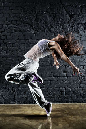 dancing pose: Young woman dancer. On wall background.