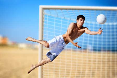 sportsman: Joven jugar al f�tbol en la playa.  Foto de archivo