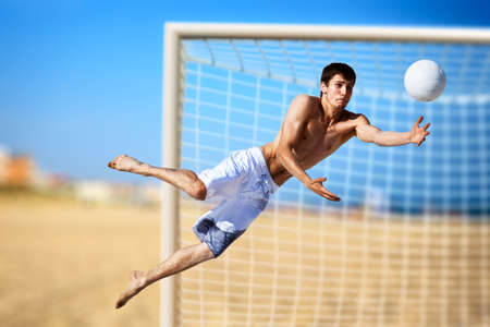 catching: Young man playing soccer on beach.