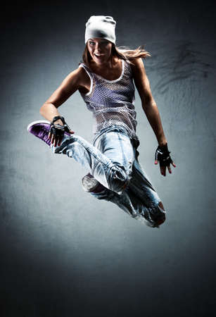 Young woman dancer jumping. On wall background. photo
