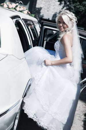 Young bride sitting to the car. Bright white colors. photo