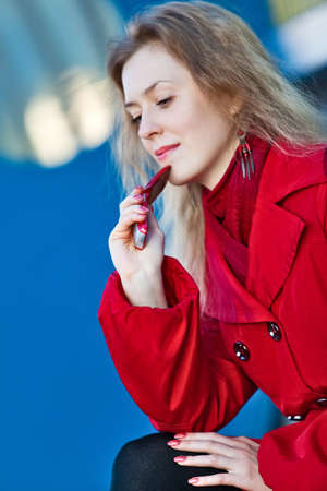 Young thoughtful woman with mobile phone portrait. Focus on hand. photo