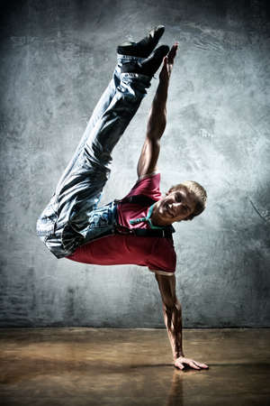 Young man break dance. On wall background. photo