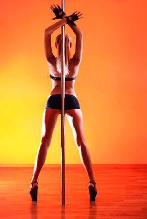 Young sexy pole dance woman. Vibrant red light. Stock Photo