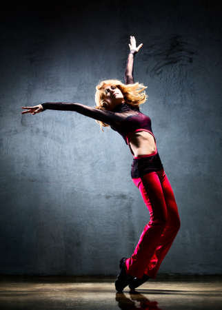 jazz dance: Young woman dancer. On wall background.