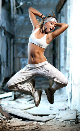 ruinous: Young woman jumping on industrial background. Stock Photo