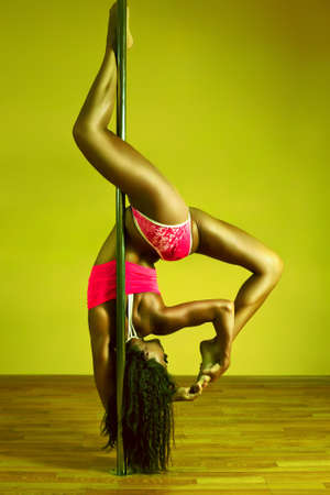 Young sexy pole dance woman. Vibrant yellow and green colors. photo