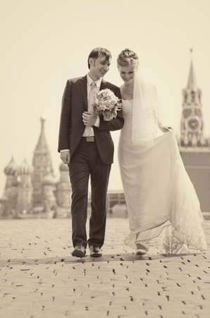 Young wedding couple walking on Red Square. Retro colors. photo