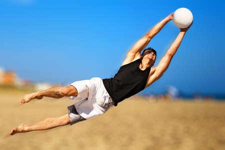 goal keeper: Jonge man spelen voet bal op strand.