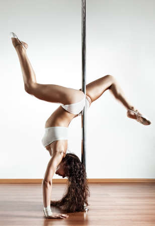 Young sexy pole dance woman. On white wall background. photo