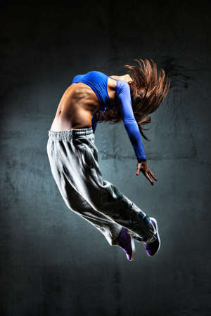 hip hop: Young woman dancer jumping. On wall background. Stock Photo