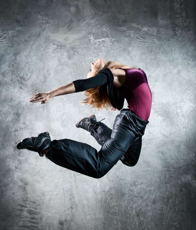 Young woman dancer jumping. On wall background. Stock Photo - 8440198