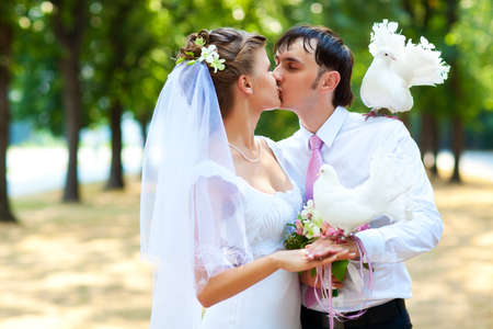 Young wedding couple with white pigeons. photo