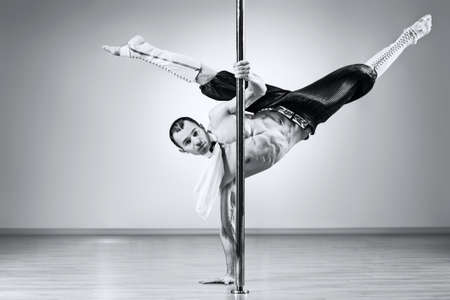 poledance: Young strong pole dance man. Black and white colors.