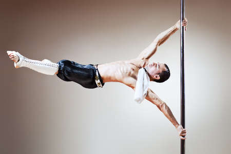 pole dance: Young strong pole dance man.