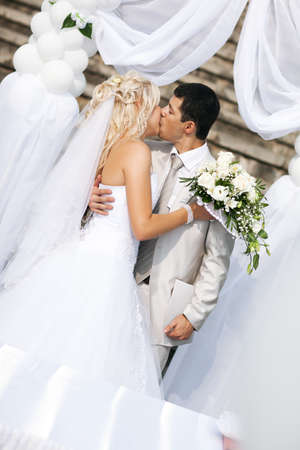 Young wedding couple kissing. White colors. photo