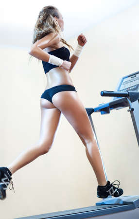 Young woman running on treadmill in gym. Stock Photo - 8569796