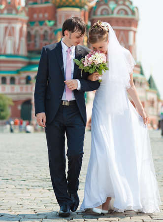 Young wedding couple walking on Red Square. photo
