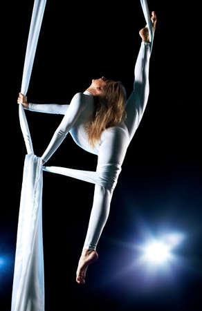 Young woman gymnast. On black background with flash effect. Stock Photo - 8602484