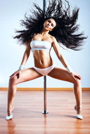 Young sexy pole dance woman shaking hair. photo