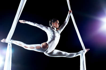 trapeze: Young woman gymnast. On black background with flash effect. Stock Photo
