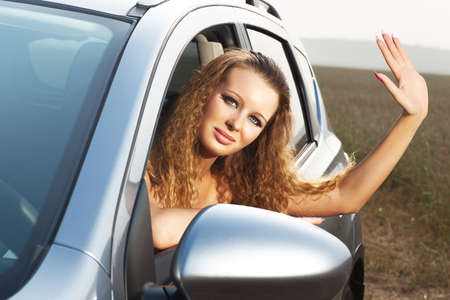 Young woman looking out of car and waving hand. Stock Photo