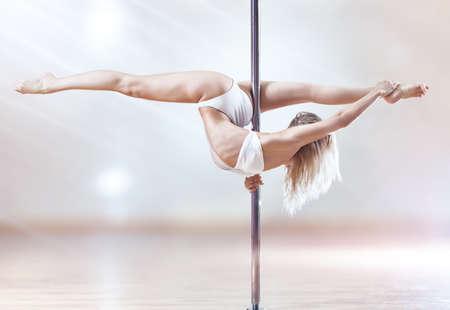 pole dancing: Femme jeune pole dance. Couleurs blancs brillants. Banque d'images