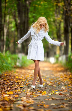 Young woman walking in autumn park. photo