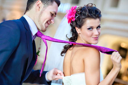 Young wedding couple indoors funny portrait.