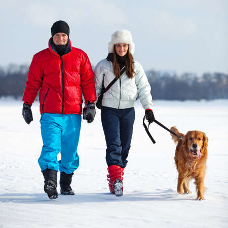 Young couple walking with dog.