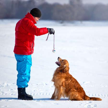 dog days: Joven jugando con perro al aire libre.