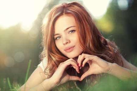 Young woman lying on grass and showing heart shape portrait. Stock Photo