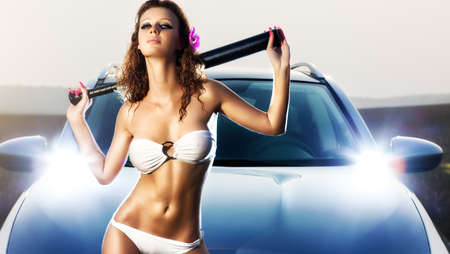 Young sexy woman with bat on car background. Stock Photo
